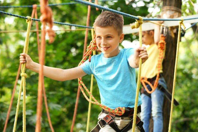 Μικρό παιδί που αναρριχείται στο πάρκο περιπέτειας στοκ εικόνες