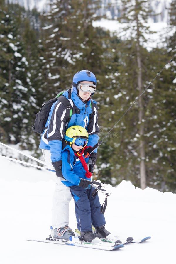 Μικρό παιδί, που ανεβαίνει έναν λόφο με έναν ανελκυστήρα επιφάνειας μαζί με το χ στοκ φωτογραφίες