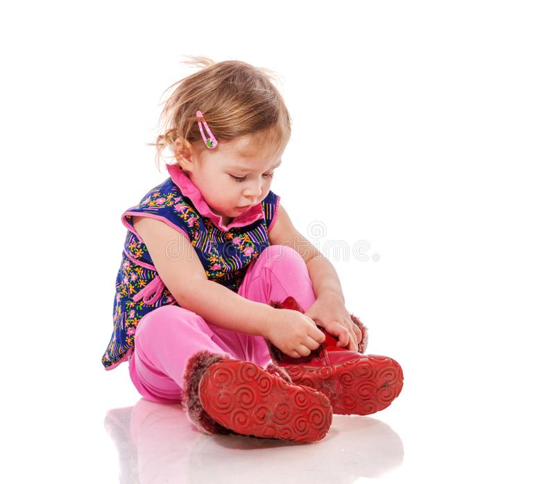 Μικρό παιδί που βάζει στα παπούτσια στοκ εικόνες