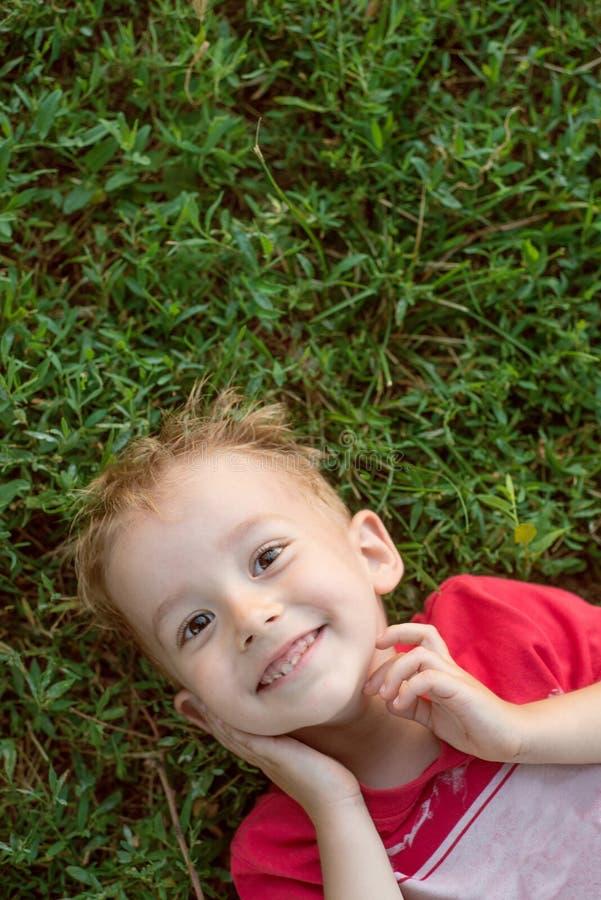 Μικρό παιδί που εξετάζει τη κάμερα που βρίσκεται στην πράσινη χλόη στοκ εικόνα με δικαίωμα ελεύθερης χρήσης