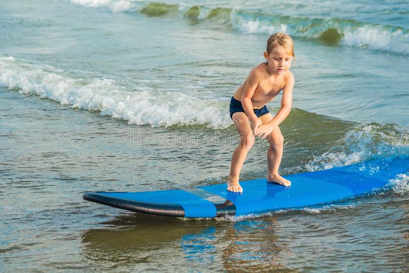 Μικρό παιδί που κάνει σερφ στην τροπική παραλία Παιδί στον πίνακα κυματωγών στο ωκεάνιο κύμα Ενεργός αθλητισμός νερού για τα παιδ στοκ εικόνες