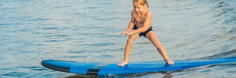 Μικρό παιδί που κάνει σερφ στην τροπική παραλία Παιδί στον πίνακα κυματωγών στο ωκεάνιο κύμα Ενεργός αθλητισμός νερού για τα παιδ στοκ φωτογραφίες με δικαίωμα ελεύθερης χρήσης