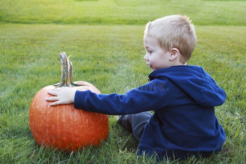 Μικρό παιδί που κρατά τη νέα κολοκύθα του για αποκριές σε ένα χλοώδες FI στοκ εικόνες