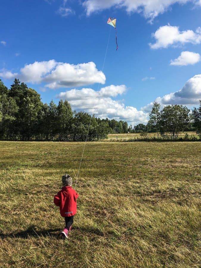 Μικρό παιδί που πετά έναν ικτίνο σε έναν θυελλώδη τομέα στοκ εικόνες