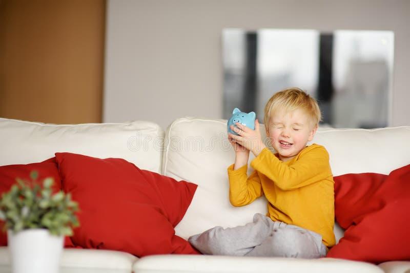 Μικρό παιδί που τινάζει ένα piggy moneybox και τα όνειρα αυτού που μπορεί να αγοράσει στοκ εικόνες