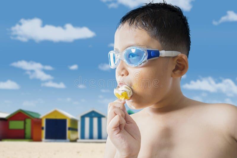 Μικρό παιδί που τρώει ένα παγωτό στην παραλία στοκ εικόνες με δικαίωμα ελεύθερης χρήσης