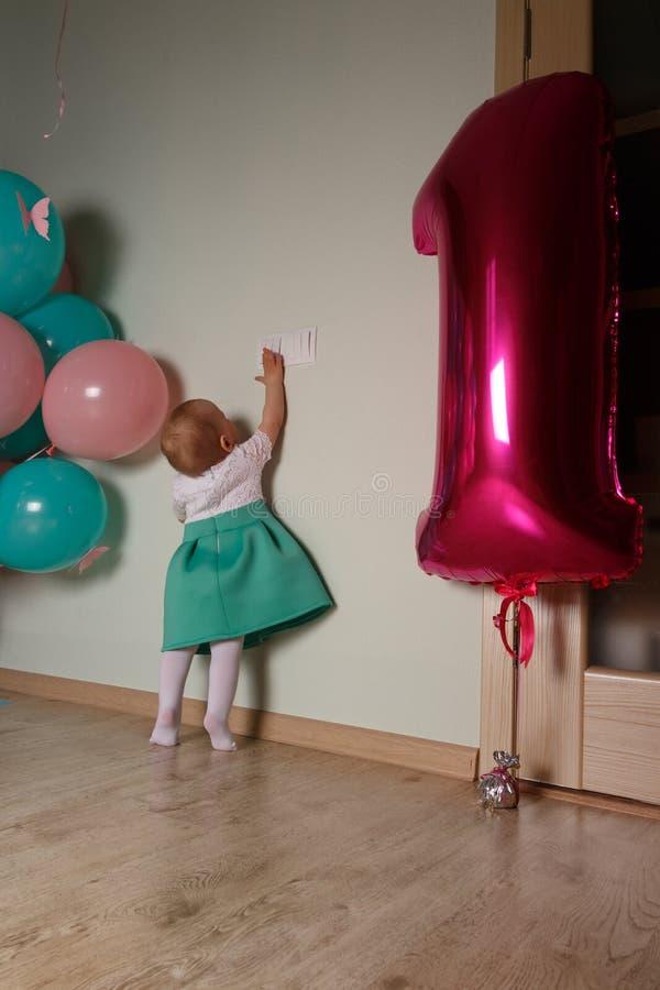 μικρό παιδί που φθάνει για έναν ελαφρύ διακόπτη, κοντινά μπαλόνια, πρώτα γενέθλια Περιέργεια κορίτσι σε ένα άσπρο μπλε φόρεμα στοκ εικόνα