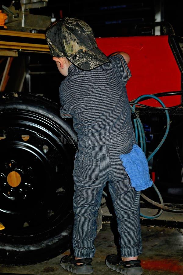 Μικρό παιδί σε μια μηχανική ομοιόμορφη εργασία αυτοκινήτων σε μια ρόδα στοκ εικόνα με δικαίωμα ελεύθερης χρήσης