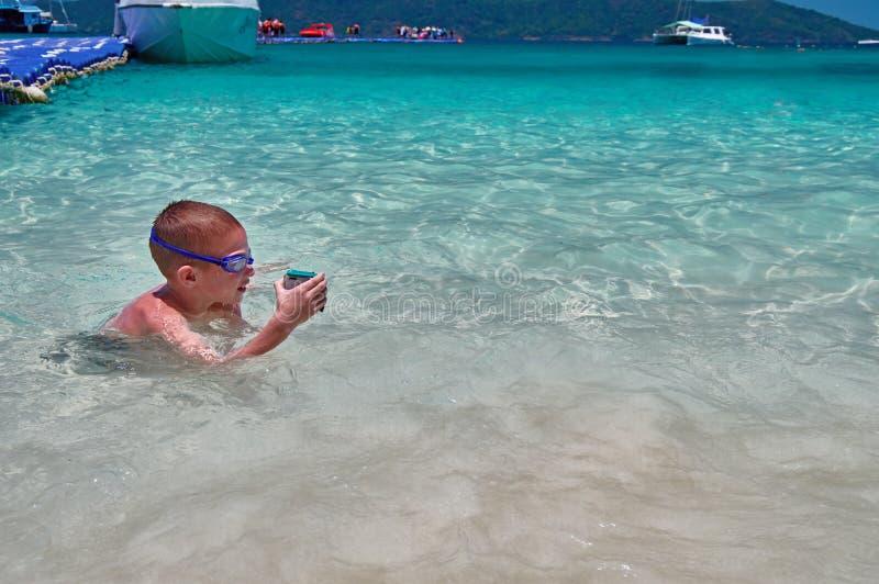Μικρό παιδί στα κολυμπώντας παιχνίδια γυαλιών στο τυρκουάζ νερό με τη κάμερα δράσης στο προστατευτικό κιβώτιο Το παιδί κολυμπά στ στοκ φωτογραφία με δικαίωμα ελεύθερης χρήσης