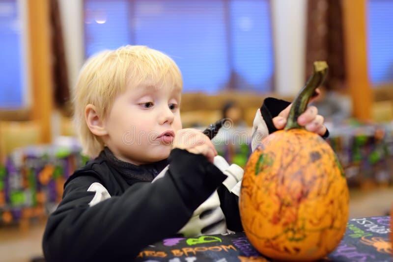 Μικρό παιδί στη τρομακτική κολοκύθα χρωμάτων κοστουμιών σκελετών στο κόμμα αποκριών για τα παιδιά στοκ εικόνα με δικαίωμα ελεύθερης χρήσης