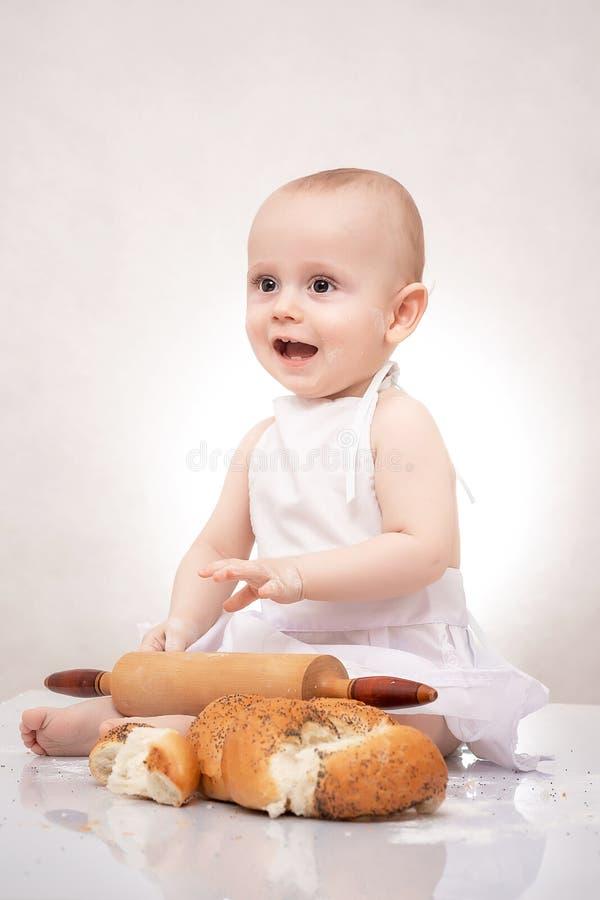 Μικρό παιδί στο κοστούμι μαγείρων στην κουζίνα με το ψωμί στοκ φωτογραφία