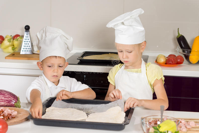 Μικρό παιδί και κορίτσι που κατασκευάζουν τη σπιτική πίτσα στοκ φωτογραφίες