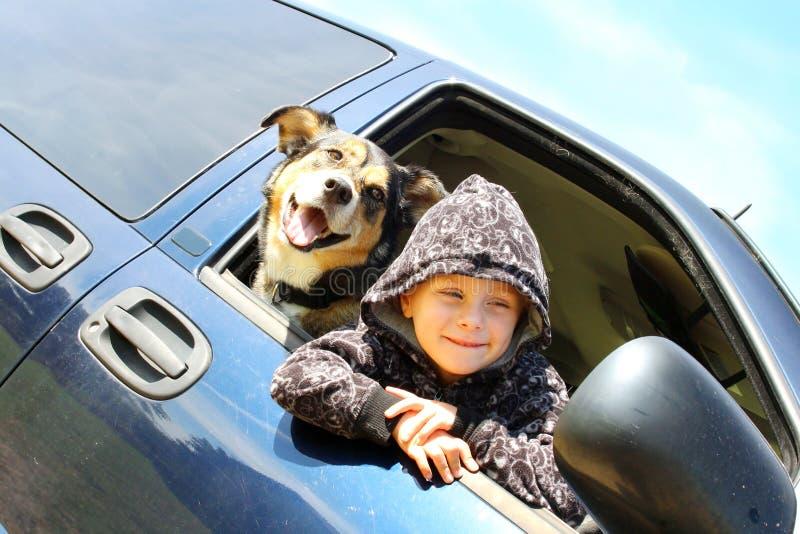 Μικρό παιδί και το σκυλί του που κρεμούν έξω το παράθυρο Minivan στοκ εικόνες