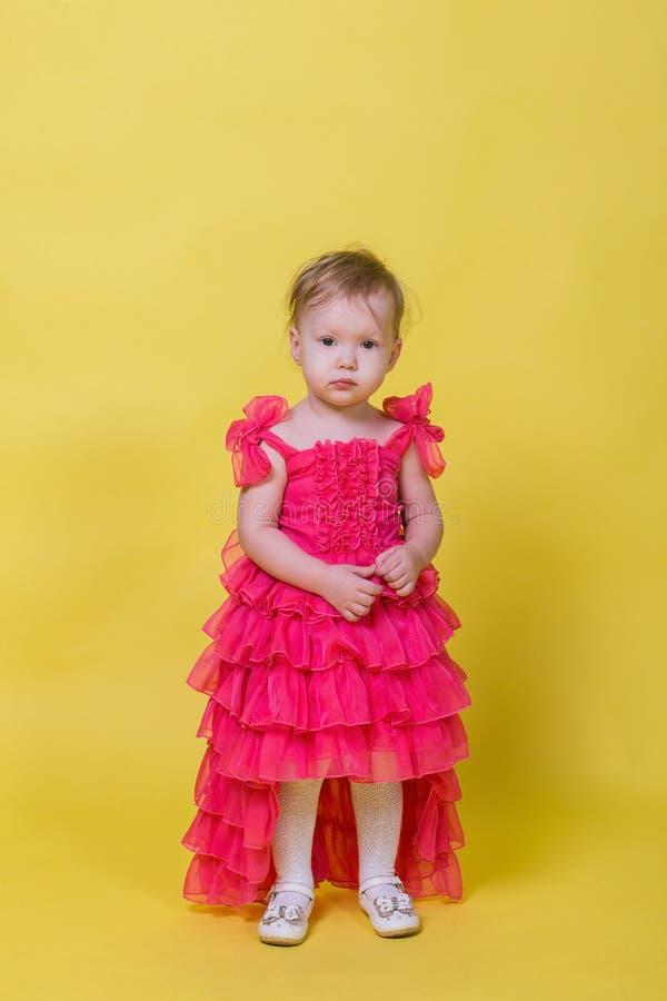 Μικρό παιδί κοριτσιών σε ένα ρόδινο φόρεμα σε ένα κίτρινο υπόβαθρο στο στούντιο στοκ φωτογραφία με δικαίωμα ελεύθερης χρήσης