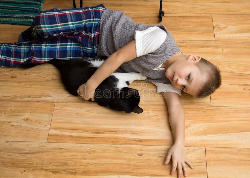Μικρό παιδί με μια γάτα στο πάτωμα στοκ εικόνα