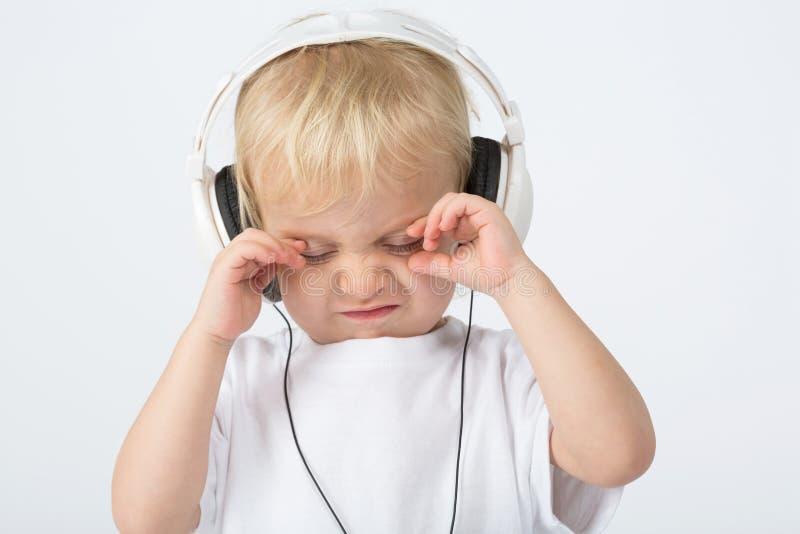 Μικρό παιδί με τα ακουστικά και δυστυχισμένος στοκ φωτογραφίες με δικαίωμα ελεύθερης χρήσης