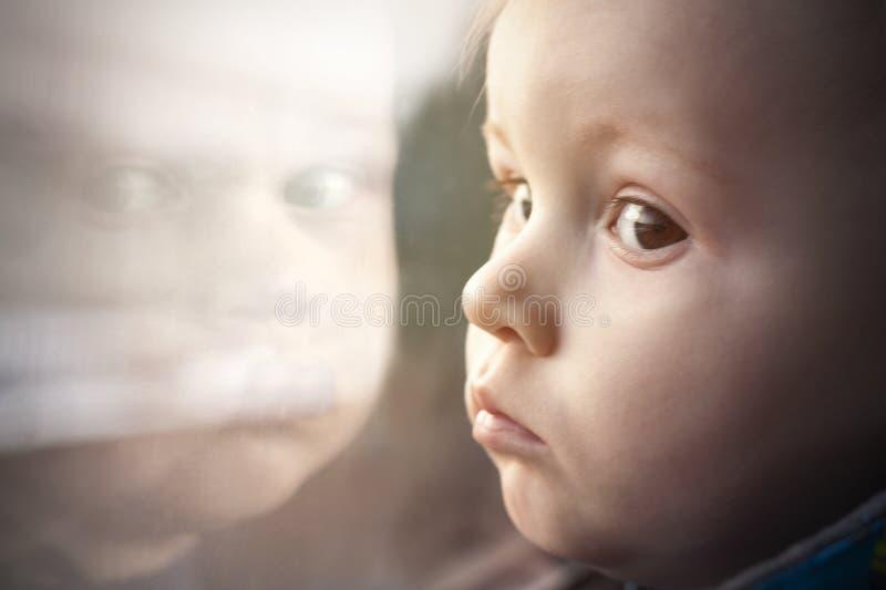 Μικρό παιδί με τα μεγάλα μάτια στην αντανάκλαση του παραθύρου στοκ φωτογραφίες