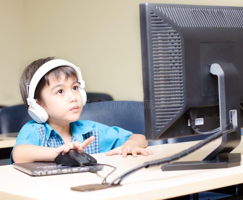 Μικρό παιδί με την κάσκα που χρησιμοποιεί τον υπολογιστή στην τάξη στοκ εικόνες