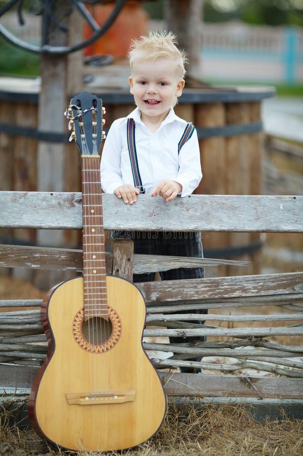 Μικρό παιδί με την κιθάρα στη θέση στοκ φωτογραφία