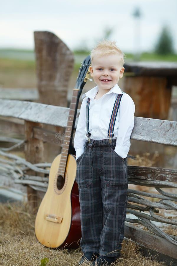 Μικρό παιδί με την κιθάρα στη θέση στοκ εικόνα
