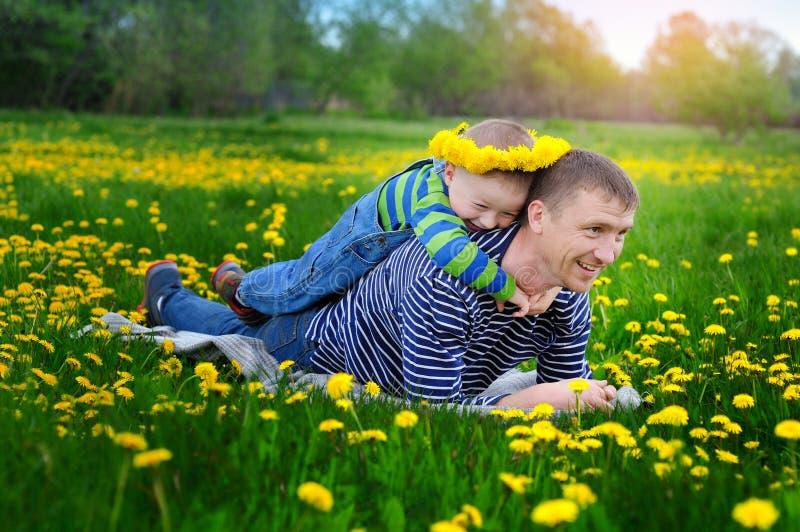 Μικρό παιδί με τον μπαμπά που περπατά σε ένα ανθίζοντας λιβάδι άνοιξη στοκ εικόνες