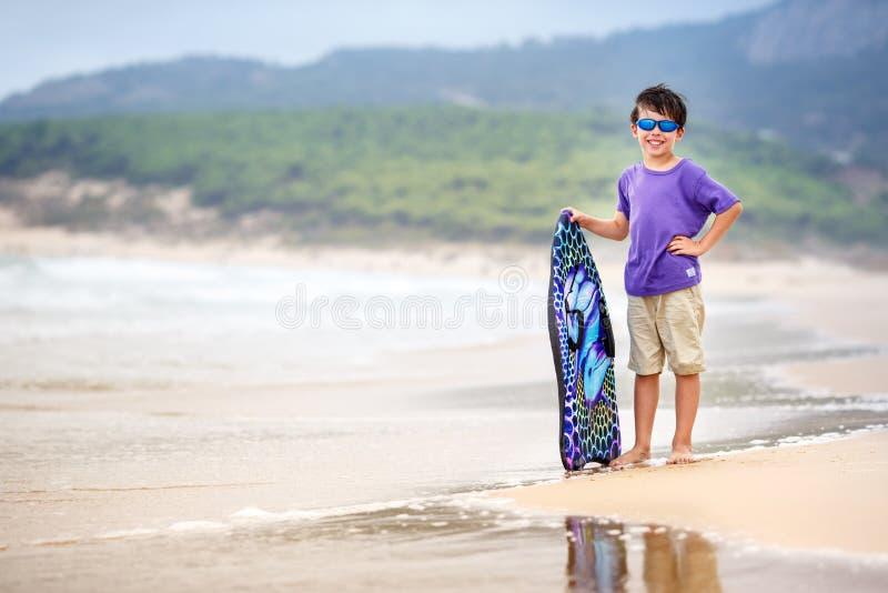 Μικρό παιδί με τον πίνακα κυματωγών στοκ φωτογραφίες