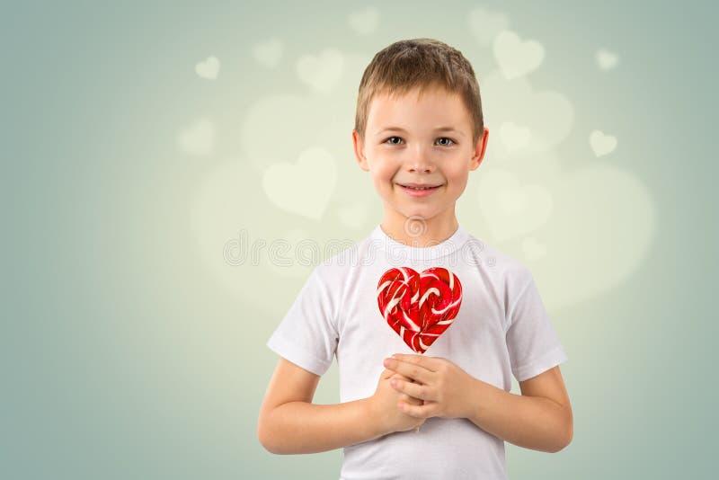 Μικρό παιδί με το κόκκινο lollipop καραμελών στη μορφή καρδιών Πορτρέτο τέχνης ημέρας βαλεντίνων ` s στοκ εικόνες