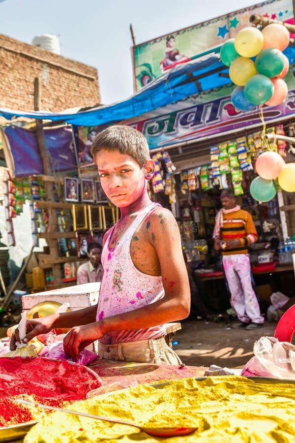 Μικρό παιδί με χρώματα τα χρωματισμένα προσώπου πώλησης χρωμάτων για το Holi στοκ φωτογραφία με δικαίωμα ελεύθερης χρήσης