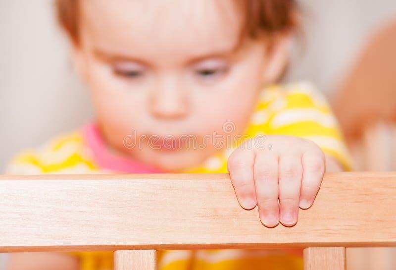 Μικρό παιδί με hairpin που στέκεται στο παχνί ανασκόπηση που θολώνεται στοκ εικόνα με δικαίωμα ελεύθερης χρήσης