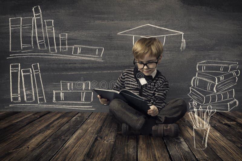 Μικρό παιδί παιδιών στα γυαλιά που διαβάζει το βιβλίο πέρα από το σχολικό μαύρο πίνακα στοκ εικόνα