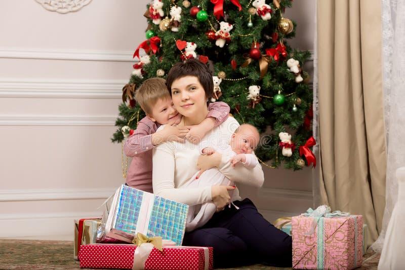 Μικρό παιδί που αγκαλιάζει τη μητέρα κοντά στο δέντρο Χριστούγεννα στοκ εικόνες