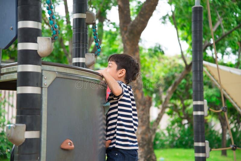 Μικρό παιδί που αναρριχείται στις υπαίθριες δραστηριότητες παιδικών χαρών στοκ εικόνα