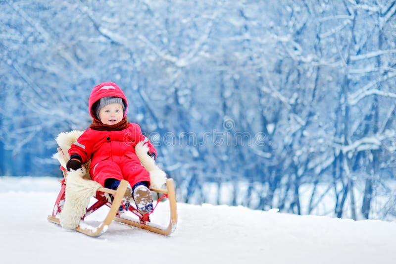 Μικρό παιδί που απολαμβάνει έναν γύρο ελκήθρων στοκ εικόνες