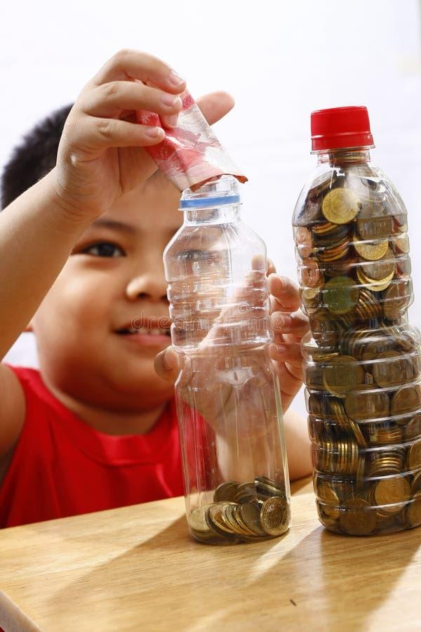 Μικρό παιδί που βάζει τα χρήματα σε ένα μπουκάλι στοκ εικόνα με δικαίωμα ελεύθερης χρήσης