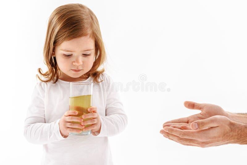Μικρό παιδί που εξετάζει glassful με το υγρό στοκ εικόνες