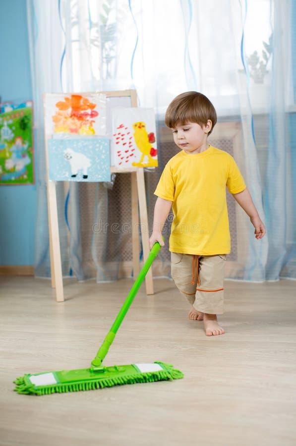 Μικρό παιδί που καθαρίζει το διαμέρισμα, που πλένει το πάτωμα στοκ εικόνα με δικαίωμα ελεύθερης χρήσης