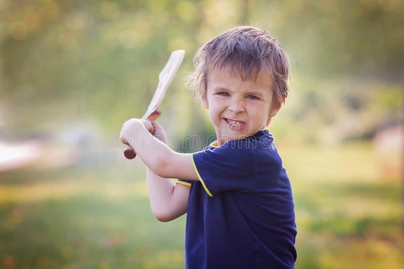 Μικρό παιδί, που κρατά το ξίφος, που λάμπει με ένα τρελλό πρόσωπο στοκ φωτογραφία