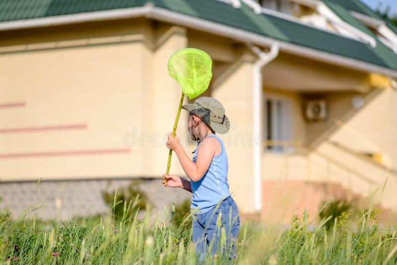 Μικρό παιδί που πιάνει τα έντομα έξω από το σπίτι του στοκ φωτογραφία με δικαίωμα ελεύθερης χρήσης