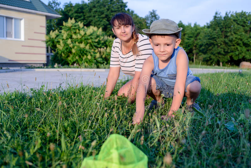 Μικρό παιδί που πιάνει τα έντομα με τη μητέρα του στοκ φωτογραφία με δικαίωμα ελεύθερης χρήσης