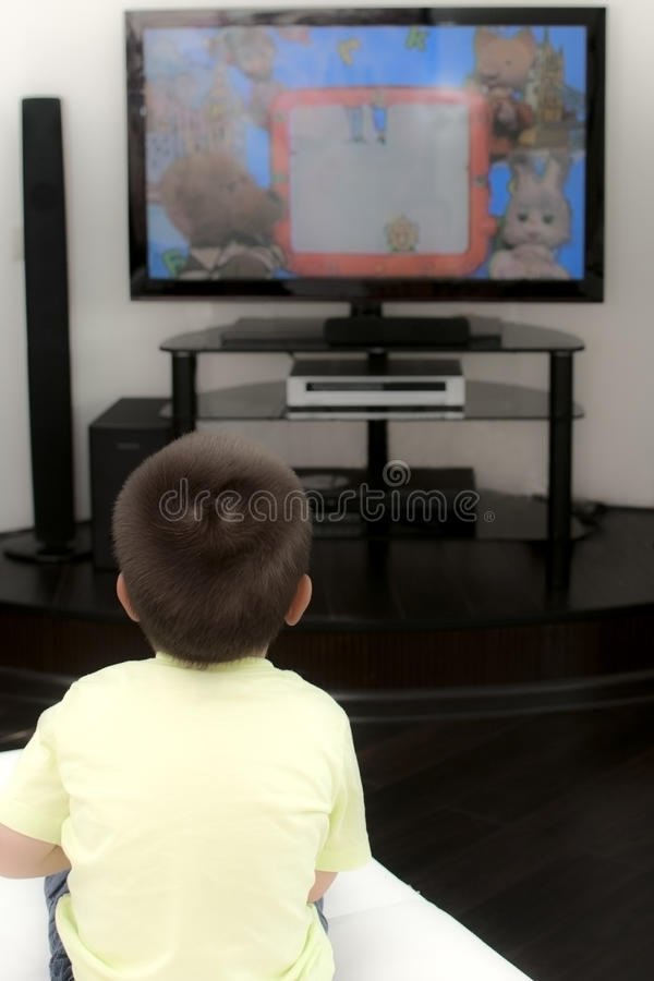 Μικρό παιδί που προσέχει τη TV στοκ εικόνα