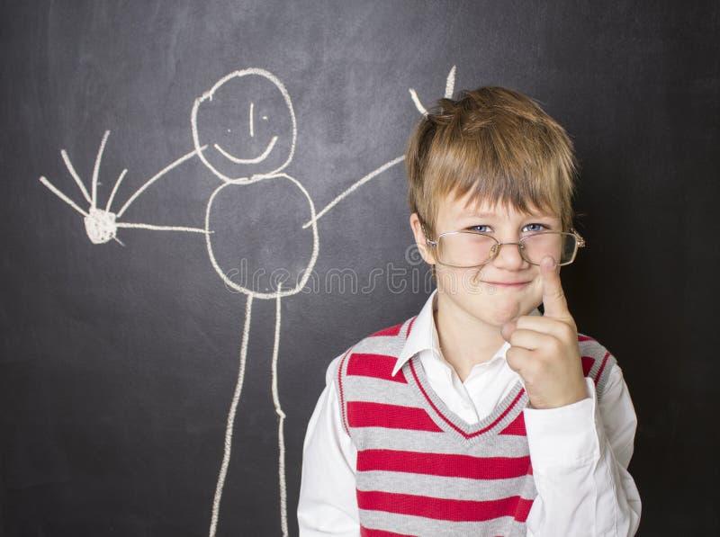 Μικρό παιδί που στέκεται κοντά στον πίνακα για το σχέδιο στοκ εικόνα