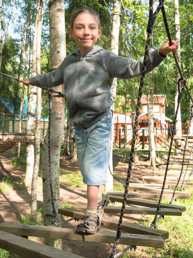 Μικρό παιδί που στέκεται σε μια ξύλινη σκάλα και που κρατά το σχοινί στοκ εικόνα