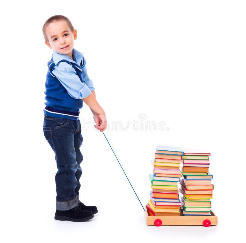 Μικρό παιδί που τραβά τα βιβλία στο κάρρο παιχνιδιών στοκ εικόνες