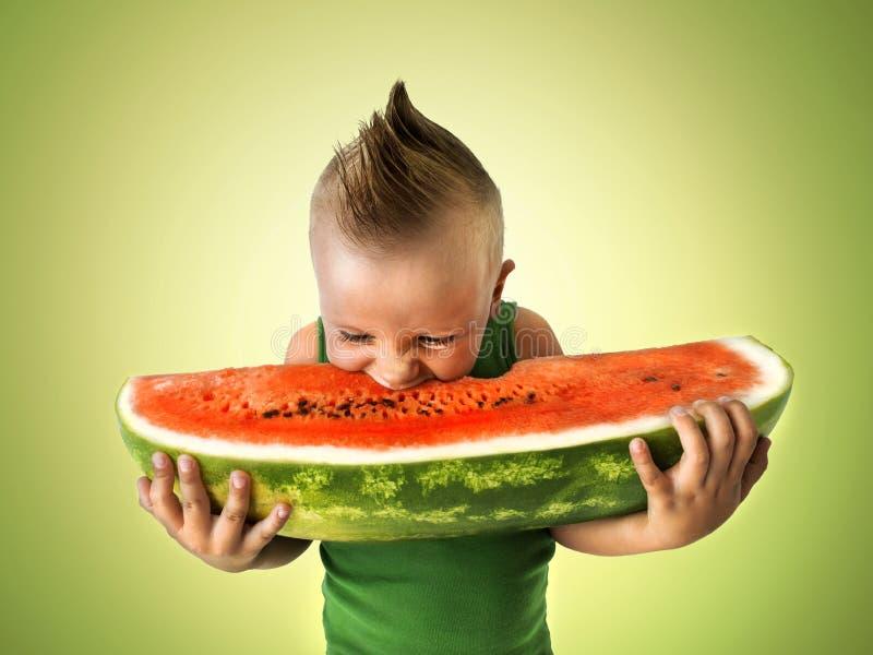 Μικρό παιδί που τρώει μια μεγάλη φέτα του καρπουζιού στοκ φωτογραφίες