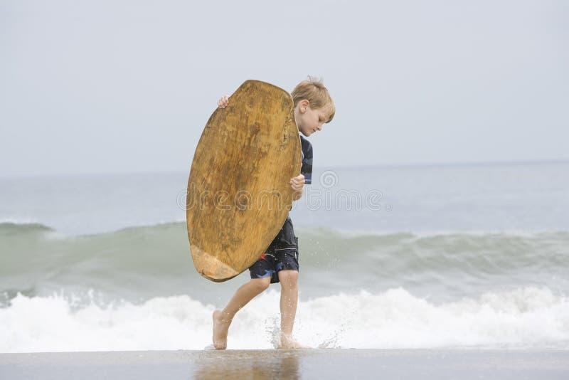 Μικρό παιδί που φέρνει Bodyboard στη θάλασσα στοκ εικόνα