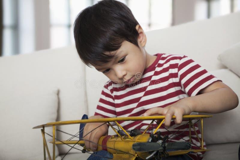 Μικρό παιδί που φαίνεται κάτω και που κρατά ένα πρότυπο αεροπλάνο, στον καναπέ στο καθιστικό στοκ φωτογραφία με δικαίωμα ελεύθερης χρήσης