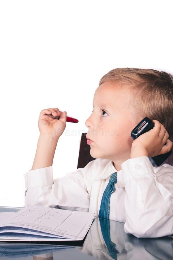 Μικρό παιδί σε ένα επιχειρησιακό κοστούμι που μιλά στα οικονομικά ζητήματα στοκ εικόνες
