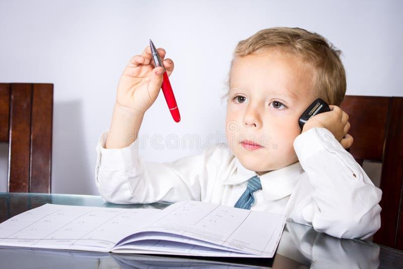 Μικρό παιδί σε ένα επιχειρησιακό κοστούμι που μιλά στα οικονομικά ζητήματα στοκ εικόνες με δικαίωμα ελεύθερης χρήσης