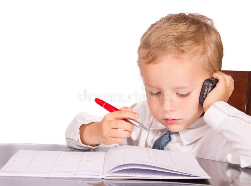 Μικρό παιδί σε ένα επιχειρησιακό κοστούμι που μιλά στα οικονομικά ζητήματα στοκ εικόνα με δικαίωμα ελεύθερης χρήσης