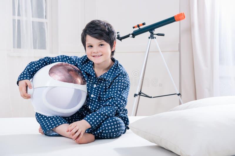 Μικρό παιδί στις πυτζάμες που κρατά τη διαστημική συνεδρίαση κρανών στο κρεβάτι στοκ εικόνες με δικαίωμα ελεύθερης χρήσης